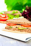 Sandwich with rye brown bread, ripe tomatoes, cucumbers and tuna fish for healthy snack on a napkin on a wooden table Royalty Free Stock Image
