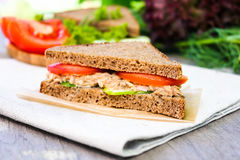 Sandwich with rye brown bread, ripe tomatoes, cucumbers and tuna fish for healthy snack on a napkin on a wooden table Stock Photography
