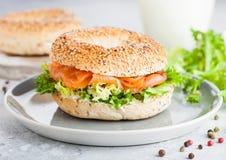 Sandwich sain frais ? bagel avec les saumons, le ricotta et la laitue dans le plat gris sur le fond clair de table de cuisine Nou image libre de droits