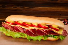 Sandwich with salami, cheese, cherry tomatoes, lettuce and musta stock photos