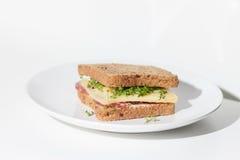 Sandwich. Salami cheese cress sandwich on a white plate stock image