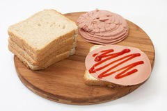 Sandwich with salami and ketchup and bread on wooden board Royalty Free Stock Photography