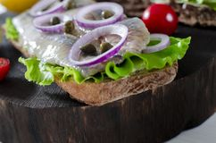 Sandwich with salted herring, butter and red onion on old rustic cutting board. Selective focus royalty free stock images
