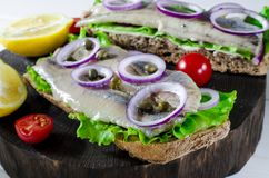 Sandwich with salted herring, butter and red onion on old rustic cutting board. Selective focus stock images