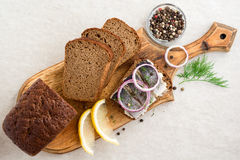 Sandwich with salted herring, butter and red onion on old rustic cutting board. Royalty Free Stock Photos