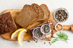 Sandwich with salted herring, butter and red onion on old rustic cutting board. Royalty Free Stock Images