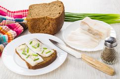 Sandwich with salted lard, pieces of lard, green onion, bread. Sandwich with salted lard in plate, pieces of lard, green onion, bread and knife on wooden table Royalty Free Stock Photos