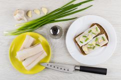 Sandwich with salted lard, pieces of lard, green onion, pepper. Sandwich with salted lard in plate, pieces of lard, green onion, pepper and knife on wooden table Royalty Free Stock Images