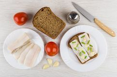 Sandwich with salted lard in plate, tomatoes, garlic, pepper, br. Sandwich with salted lard in plate, tomatoes, garlic, pepper, rye bread and knife on wooden Stock Photos