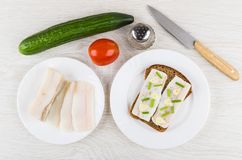 Sandwich with salted lard, tomato, cucumber, pepper and knife. Sandwich with salted lard in plate, tomato, cucumber, pepper and knife on wooden table. Top view Royalty Free Stock Photography