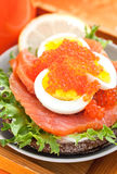 Sandwich with salted salmon, egg and red caviar Stock Images