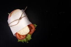 Sandwich with sausage bandaged twine on a black background. With Royalty Free Stock Image