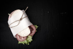Sandwich with sausage bandaged twine on a black background. With Stock Images