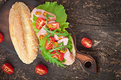 Sandwich with sausage, lettuce, tomato and arugula Stock Image
