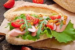 Sandwich with sausage, lettuce, tomato and arugula Stock Photo