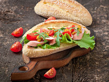 Sandwich with sausage, lettuce, tomato and arugula Royalty Free Stock Photos