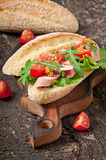 Sandwich with sausage, lettuce, tomato and arugula Stock Photos
