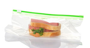 Sandwich with sausage in plastic bag isolated on white background. Stock Image