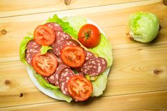 A sandwich with sausage and a tomato on lettuce leaves. A sandwich with sausage and a tomato on lettuce leaves on a white plate. Wooden background Stock Images