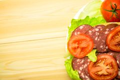A sandwich with sausage and a tomato on lettuce leaves. A sandwich with sausage and a tomato on lettuce leaves on a white plate. Wooden background Stock Photos