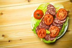 A sandwich with sausage and a tomato on lettuce leaves. A sandwich with sausage and a tomato on lettuce leaves on a white plate. Wooden background stock photography