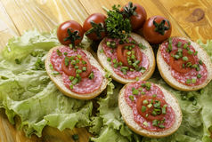 Sandwich with sausage and tomatoes. On the leaves of lettuce royalty free stock images