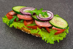 Sandwich with sausage and vegetables on whole grain bread Stock Images