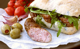 Sandwich with  sausages, greens, cherry tomatoes and olives Stock Photography
