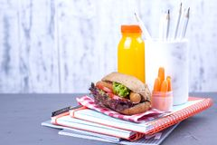 A sandwich with sausages and salad in a lunch box with vegetables and fresh juice in a bottle. Delicious and healthy lunch for