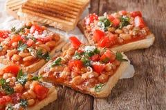 Sandwich savoureux avec des haricots blancs, des tomates, le fromage et des clos d'herbes Photo libre de droits