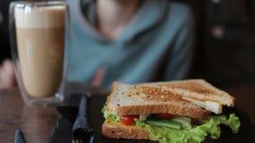 Sandwich savoureux avec des légumes Café potable de femme et consommation en café banque de vidéos