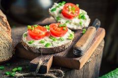Sandwich savoureux avec du fromage de fromage, les tomates-cerises et la ciboulette Photographie stock