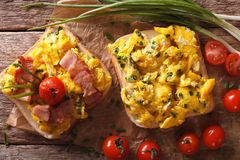 Sandwich with scrambled eggs, bacon and tomatoes close-up. horiz Stock Photography