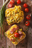Sandwich with scrambled eggs, bacon and tomatoes close-up. Verti Royalty Free Stock Images