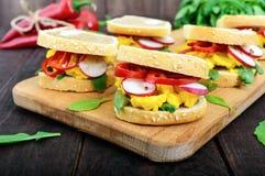 Sandwich with scrambled eggs, rucola, radish, paprika kapi and flax seeds Royalty Free Stock Photos