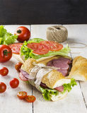 Sandwich with sesame bread. Tomato, cucumber, meat, cheese, lettuce on a wooden background Royalty Free Stock Image