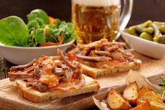 Sandwich with shredded pork, roasted potatoes and salad. On wooden table stock photo