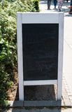 Sandwich sign blackboard with white wooden frame. Blackboard shows shadows of erased white chalk. Sandwich sign restaurant blackboard with white wooden frame stock image