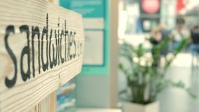 A sandwich sign written on a wooden board. Nearby there are blurred people stock footage