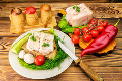 Sandwich with slice of rye bread, fresh pork lard and parsley in the plate, fresh produce, vegetables on wooden table. Royalty Free Stock Photo