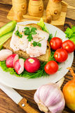 Sandwich with slice of rye bread, fresh pork lard and parsley in the plate, fresh produce, vegetables on wooden table. Stock Photos
