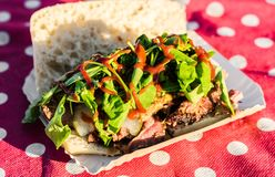 Sandwich with slow cooked smoked beef and bbq sauce at a street food market. Sandwich with slow cooked smoked beef and bbq sauce royalty free stock images