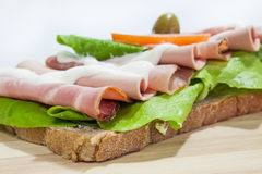 Sandwich with smoked ham, lettuce, olive and tomato Royalty Free Stock Image