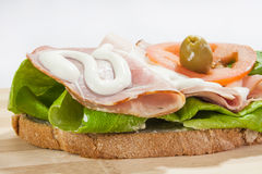 Sandwich with smoked ham, lettuce, olive and tomato Stock Photos