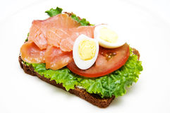 Sandwich with smoked salmon. A sandwich with lettuce, smoked salmon tomato and  quail egg on a white plate Royalty Free Stock Photo