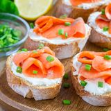 Sandwich with smoked salmon and cream cheese on wooden board, square. Format Stock Photo