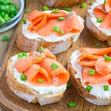 Sandwich with smoked salmon and cream cheese on wooden board, square format. Sandwich with smoked salmon and cream cheese on wooden board, square Royalty Free Stock Photography