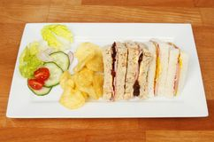 Sandwich snack platter. Ham mustard and pickle sandwiches with potato crisps and salad garnish on a plate on a wooden tabletop Royalty Free Stock Photo