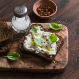 Sandwich with soft cheese, olive oil and basil, served on olive cutting board on dark wooden surface. Royalty Free Stock Photos