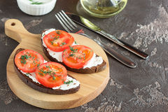 Sandwich with soft cheese and tomatoes. On dark bread Royalty Free Stock Images